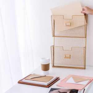 WHITE DESK WITH FOLDERS NEATLY STORED IN WIRE BASKETS HANGING ON WALL