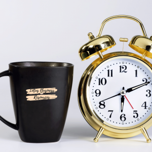 PICTURE OF BLACK COFFEE MUG with Lotus Business Resources logo standing next to a golden 2 bell alarm clock set at 6:10