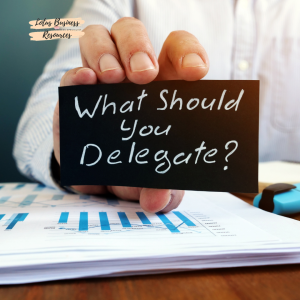 a hand holding a mini chalkboard with What Should You delegate written on it