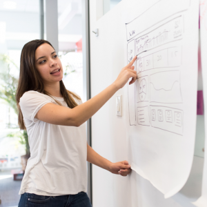 WOMAN STANDING AT A FLIPCHART POINTING TO WHAT IS WRITTEN ON IT